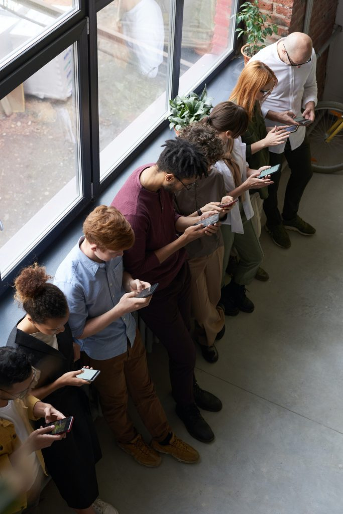line of people texting on their phones