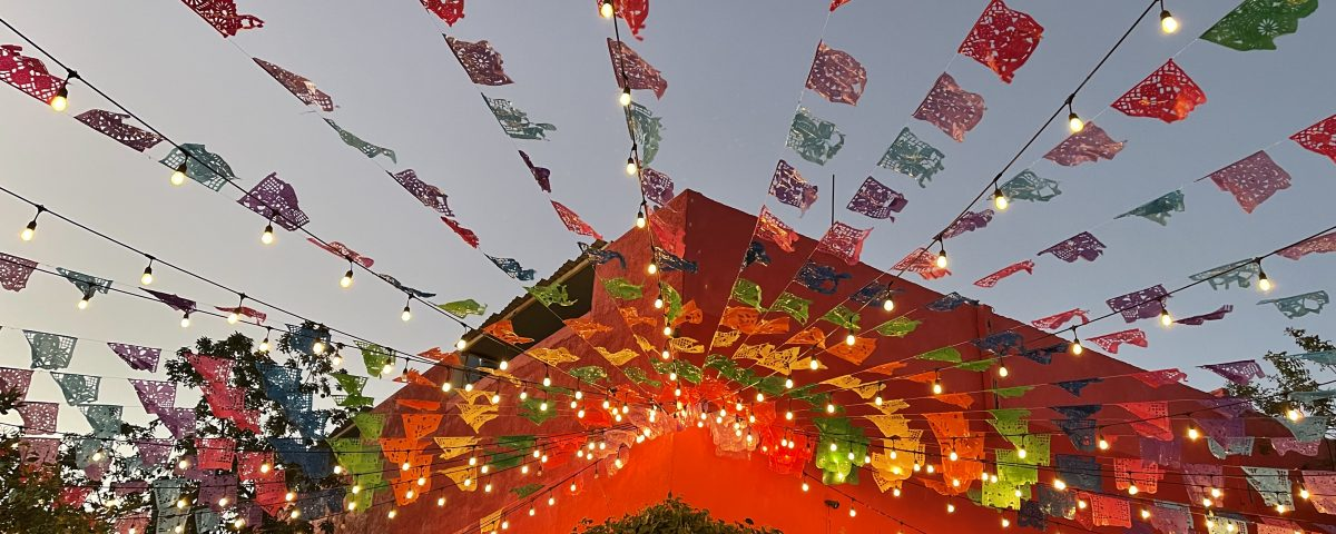 flags waving at red building at los tres gallos in cabo san lucas mexico