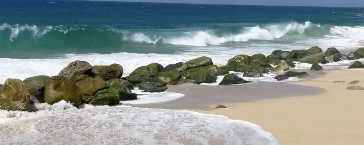 waves crashing to the shore along the beach at cabo san lucas